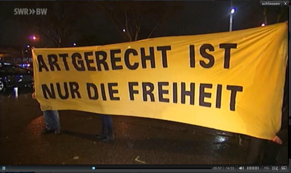 Grüne Demo vor einem Zirkus. Vor dem Zirkuszelt wurde von der Karlsruher Ortsgruppe der Grünen dazu ein Protesttransparent entrollt mit dieser Aufschrift. Wann stehen diese eifernden Leute vor Bio-Ställen? Wann merken die Bioverbände, mit wem sie da im Bette sind? (Quelle SWR)