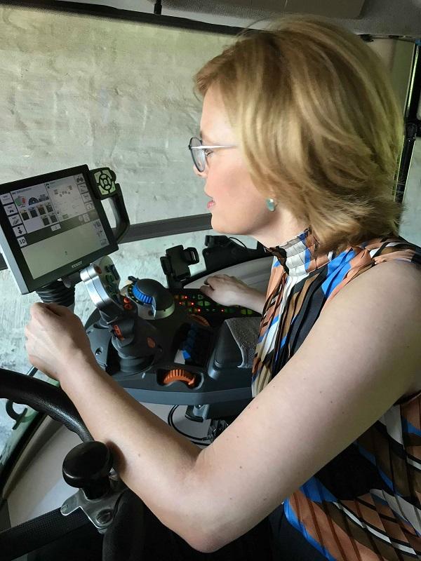 Julia Klöckner sitzt in der Kabine eines großen Schleppers der Marke Fendt und inspiziert die umfassenden technischen Geräte und Bedienungsbildschirme