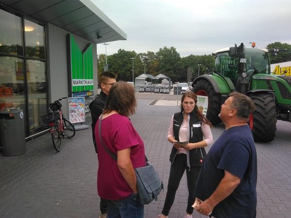 Agrarscoutin Schillingmann unterhält sich vor vom Supermarkt mit Verbrauchern