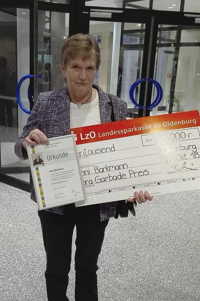 Anni Barkmann präsentiert ihre Urkunde uns den überdimensional großen Scheck über 1000€