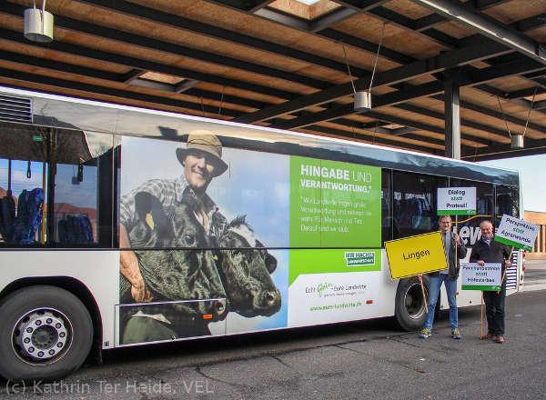 Georg Meiners und Bernhard Barkmann posieren mit Demonstrationsschildern vor einem Bus mit landwirtschaftlichem Werbeaufdruck