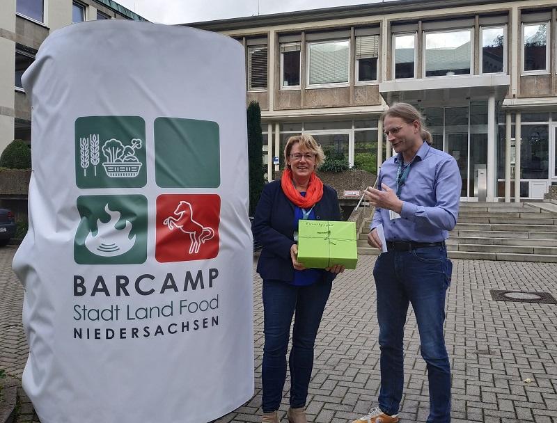 """Bernhard Barkmann überreichte der Ministerin am Rande des Barcamps """"Stadt land Food"""" ein grünes Agrarpaket"""