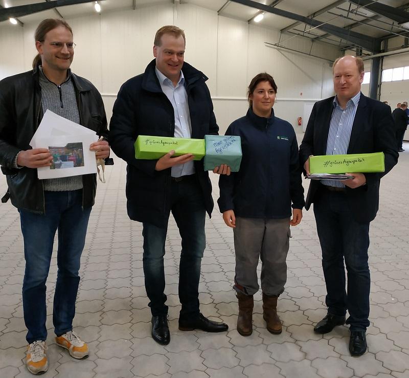 Gruppenfoto mit den beiden Politikern und Bäuerin Frentjen, die auch ein grünes Agrarpaket überreichte