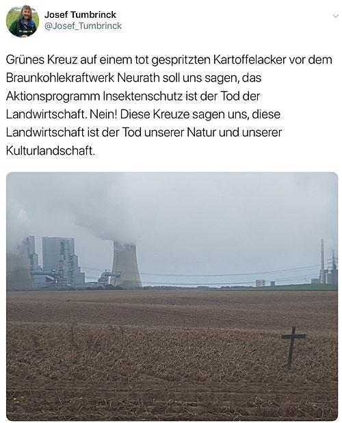 Kartoffelacker mit grünem Kreuz, im Hintergrund ein Kraftwerk.