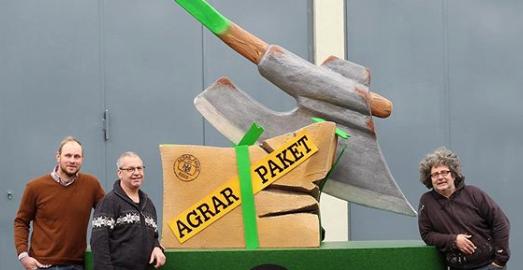 Drei Landwirte bauen einen Motivwagen mit grünem Kreuz, das ein Agrarpaket zerstört.