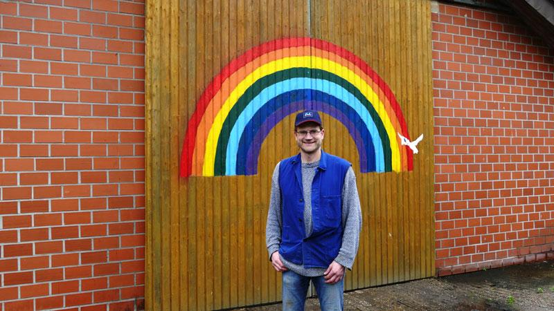 Agrarblogger Bernhard Barkmann vor der Tür des Bullenstalles, die mit einem großen Regenbogen verziert ist