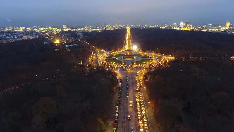 Treckendemo in Berlin. Die Lichter der Schlepper leuchten an der Siegessäule in der Dämmerung